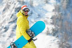 view of sportsman with snowboard standing in the forest - stock photo