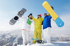 portrait of happy three sportsmen raising their snowboards - stock photo