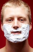 Portrait of young man with foam on face looking upwards Stock Photos