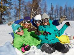 portrait of four laughing teenagers in ski goggles sitting on snow - stock photo