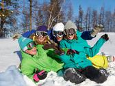 Stock Photo of portrait of four laughing teenagers in ski goggles sitting on snow