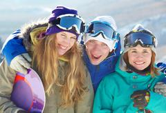 portrait of three cheerful friends in ski goggles looking at camera and smiling - stock photo