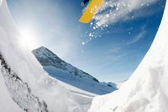 Stock Photo of photo of jumping snowboarder over mountainside on winter resort