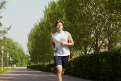 portrait of a young man jogging in park - stock photo