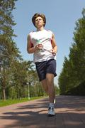 portrait of a young man jogging in park in summer - stock photo
