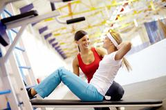 a girl pumping abdominal muscles in gym with help of her girlfriend - stock photo