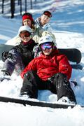 Stock Photo of portrait of happy friends snowboarding during winter vacations