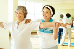 Portrait of sporty female supporting her friend while doing physical exercise in Stock Photos