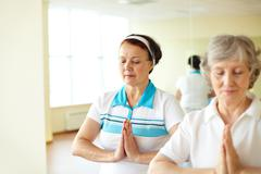 portrait of two aged females doing yoga exercise for balance in sport gym - stock photo