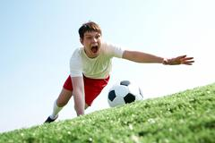 image of soccer player falling down while looking at ball and shouting - stock photo
