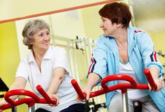 Stock Photo of portrait of senior females doing physical exercise on special equipment in gym