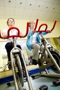 portrait of senior females doing physical exercise on special equipment - stock photo