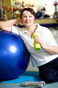 portrait of aged woman with bottle of water sitting by blue ball - stock photo