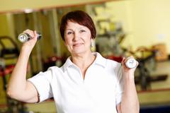Stock Photo of portrait of aged woman doing physical exercise with barbells