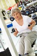 Photo of active woman pumping muscles on special equipment Stock Photos