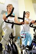 portrait of senior females doing physical exercise on special equipment in club - stock photo