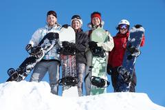 portrait of happy company of guys and girl with snowboards - stock photo