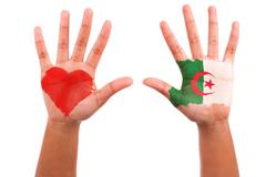 african hands with a painted heart and algerian flag, i love algeria concept - stock photo