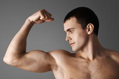 Close-up of strong muscular man over grey background Stock Photos
