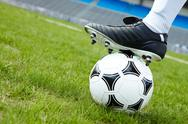 Horizontal image of soccer ball in green grass with foot of player touching it Stock Photos