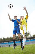 Two footballers jumping and looking at ball on grass-field during game Stock Photos