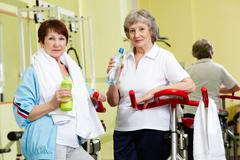 portrait of senior females with plastic bottles looking at camera in gym - stock photo
