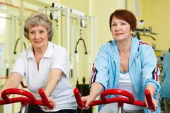 portrait of two senior women training on exercise bicycle - stock photo
