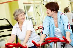 Stock Photo of portrait of two active seniors sitting on exercise bicycles