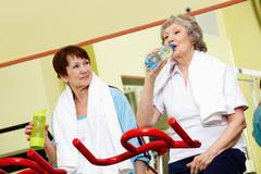 senior women taking a drink in gym - stock photo