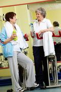 Two senior women communicating in gym Stock Photos