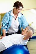 senior woman doing abdominal exercises with her instructor in gym - stock photo