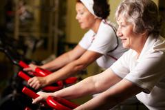 two senior women training in gym - stock photo
