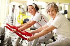 portrait of two senior women in gym - stock photo