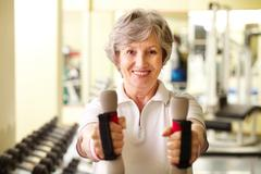 Portrait of pretty senior woman exercising with dumbbells Stock Photos