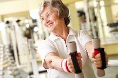 good-looking senior woman training in gym - stock photo