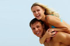 Photo of happy girl embracing handsome guy against blue sky at summer Stock Photos
