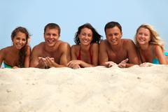 Portrait of happy girls and guys lying on sand on summer vacation Stock Photos