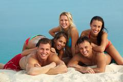 Portrait of group of friends lying on sand on sunny day and having rest Stock Photos