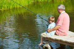 Photo of grandfather and grandson sitting on pontoon and fishing on weekend Stock Photos