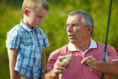 photo of grandfather telling his grandson about the fish caught by them - stock photo