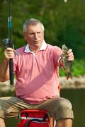 photo of senior man catching fish on weekend - stock photo