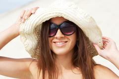 portrait of pretty young lady in hat touching it and looking at camera through s - stock photo