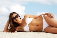 Image of female in white bikini sunbathing on sandy beach Stock Photos