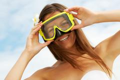 image of pretty girl looking at camera through goggles - stock photo