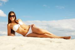 image of female in white bikini sunbathing on sandy beach - stock photo