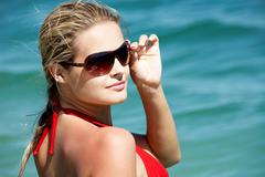 young woman in shades at sea - stock photo