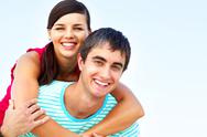 Stock Photo of portrait of a young couple, the girl is on her boy's back