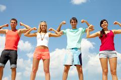 four happy friends showing their muscles - stock photo