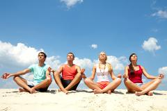 four young people sitting on sand and meditating - stock photo