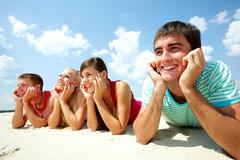 four young friends lying on sand and smiling - stock photo